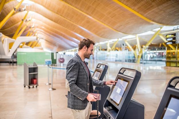 Счастливый человек с помощью машины регистрации в аэропорту, получить посадочный талон.