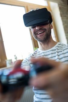 Счастливый человек с помощью виртуальной реальности гарнитуры и играть видеоигры