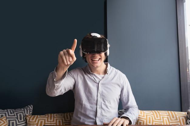Uomo felice utilizzando le cuffie da realtà virtuale