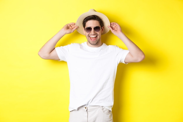 Uomo felice in vacanza, con cappello di paglia e occhiali da sole, sorridente in piedi su sfondo giallo.