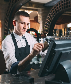 Happy man or waiter in apron at counter with cashbox working at bar or coffee shop