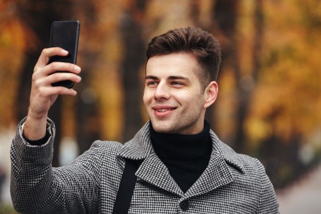 Happy man warmly dressed taking photo of nature or making selfie using black smartphone, while walking in park