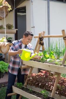 그의 정원을 급수하는 행복 한 사람