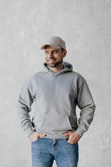 Счастливый человек в кепке и серой толстовке с капюшоном