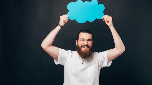 Счастливый человек с бородой держит над головой бумажное облако.