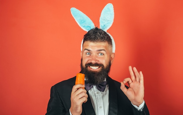 Happy man wearing bunny ears with carrot isolated on red background