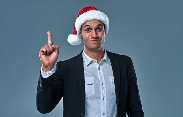 회색 배경 위에 크리스마스 모자를 쓰고 행복한 남자. 제품을 제시하고 손가락으로 가리키는 동안 놀랍고 웃는 남자. 크리스마스 홍보, 공간 복사.