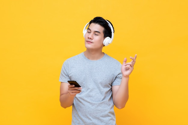 Happy man wearing headphones listening to music from smartphone with eye closed