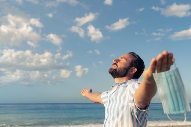 푸른 하늘 배경 야외 의료 마스크를 쓰고 행복 한 사람