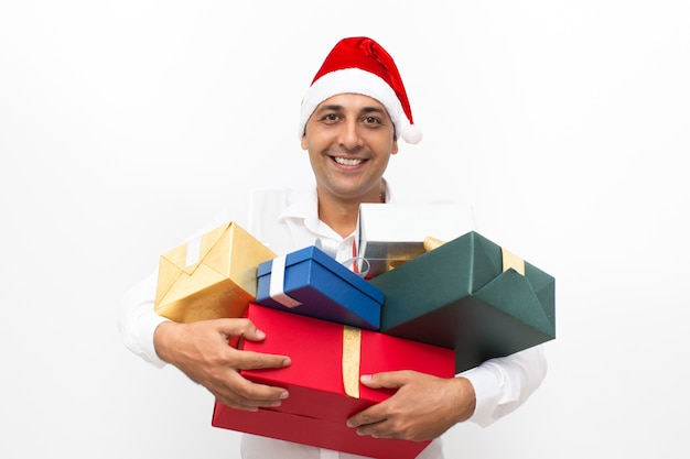 Happy man wearing santa hat and holding gift boxes