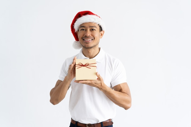 Happy man wearing santa hat and showing gift box