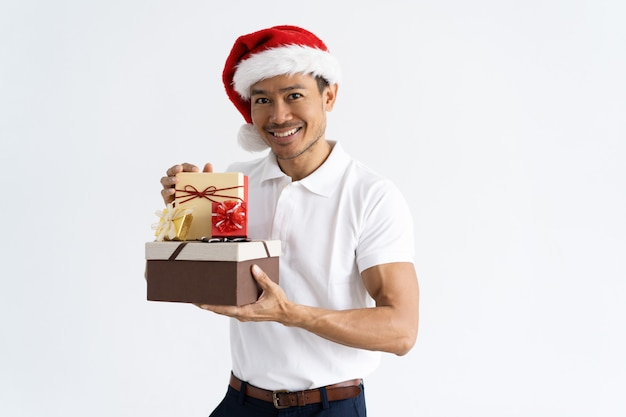 Happy man wearing santa hat and showing gift boxes