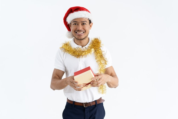 Happy man wearing santa hat, tinsel and holding gift box