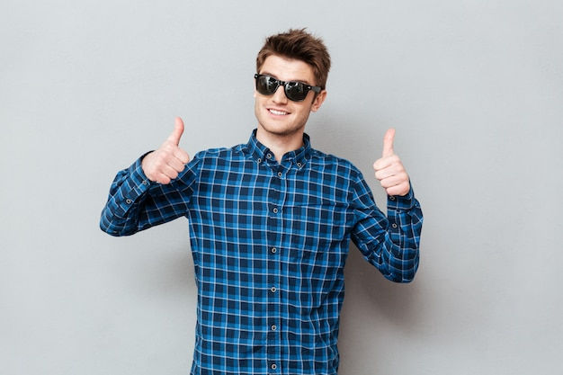 Happy man wearing sunglasses showing thumbs up.