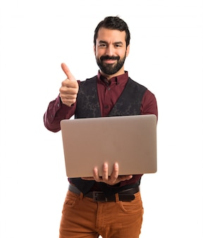 Happy man wearing waistcoat with laptop