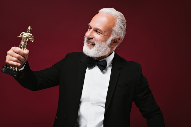 Happy man in white shirt and jacket looks at oscar statuette