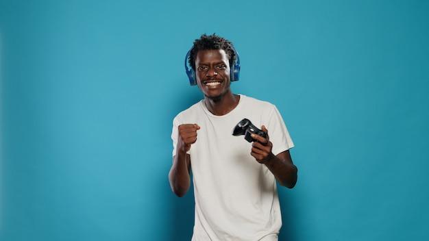 Счастливый человек выигрывает в видеоиграх с джойстиком на консоли