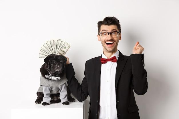 Uomo felice che vince denaro, indossa un costume e mostra dollari vicino al suo simpatico cane nero in tuta, in piedi su sfondo bianco