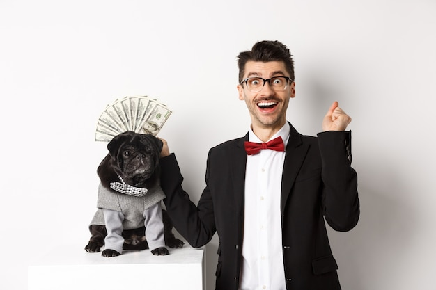 Happy man winning money, wearing costume and showing dollars near his cute black dog in suit, standing over white.