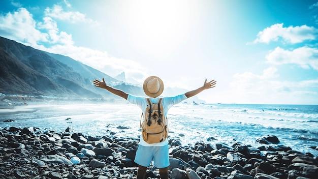 해변에서 자유를 즐기고 위로 팔을 가진 행복한 사람