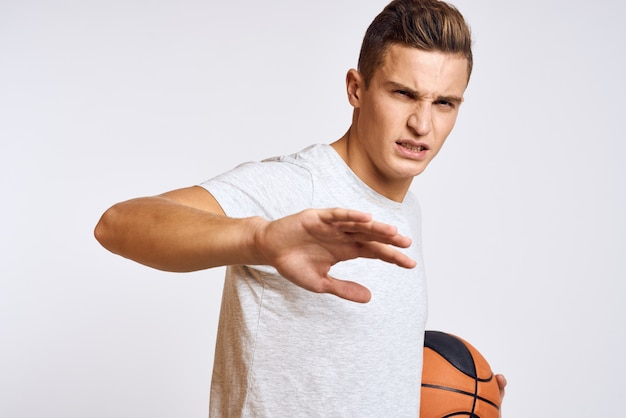 Happy man with ball in hand and in white t-shirt on light background gesturing with hands cropped