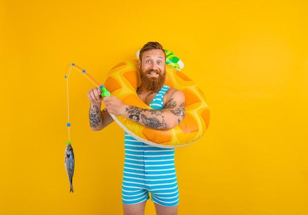수염과 풍선 도넛을 가진 행복한 남자가 물고기를 잡는다