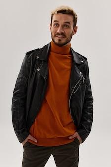 あごひげと革のジャケットオレンジ色のセーターパンツモデルと幸せな男