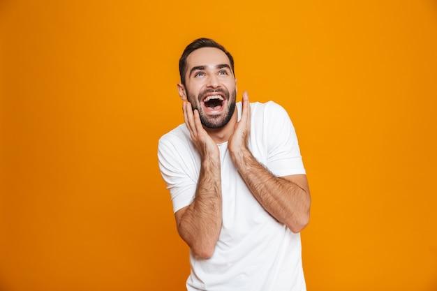 Счастливый человек с бородой и усами смеется стоя, изолированный на желтом