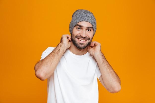 Счастливый человек с бородой и усами улыбается стоя, изолированный на желтом