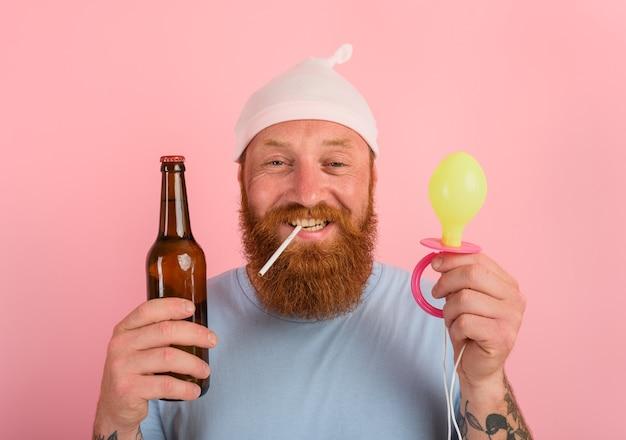 수염과 문신을 한 행복한 남자는 맥주를 손에 들고 갓난 아기처럼 행동합니다