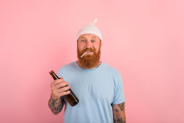 あごひげと入れ墨のある幸せな男は、手にビールを持った小さな新生児のように振る舞います