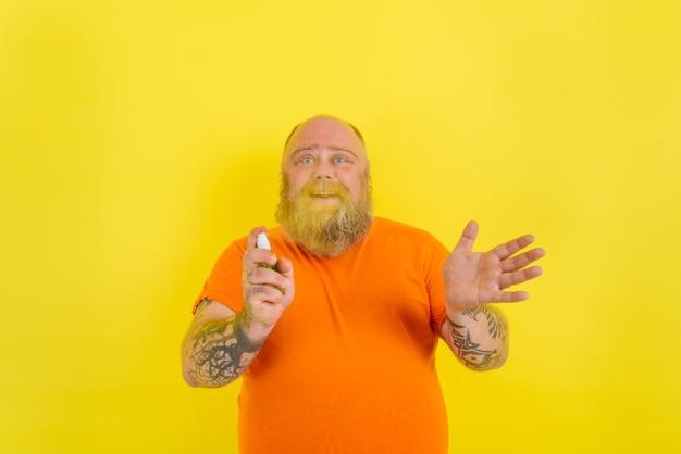 あごひげと入れ墨のある幸せな男は、covidに対して手をきれいに保持します