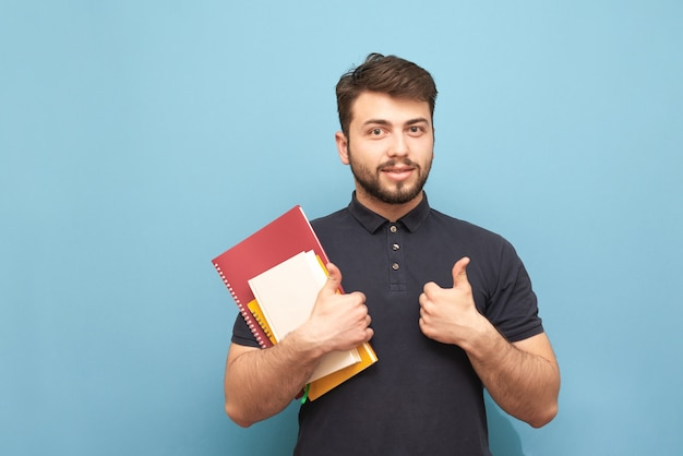 Happy man with a beard and books and notebooks in his hand shows a thumbs up and smiles, isolated on blue