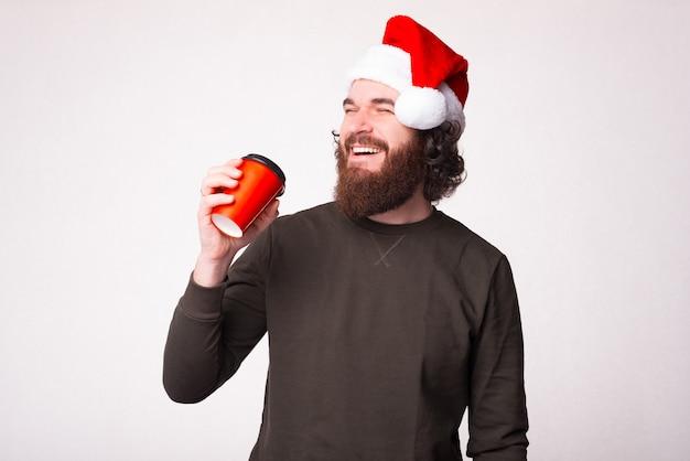 빨간 컵에서 커피를 마시고 빨간 크리스마스 모자를 쓰고 수염을 가진 행복한 사람