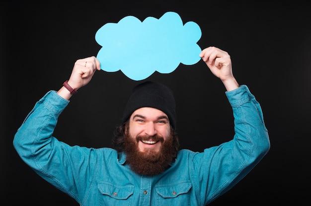 頭上に空の青い雲を保持しているひげを持つ幸せな男