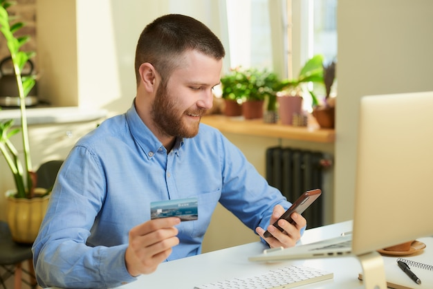 A happy man with a beard searching for products in online stores on a smartphone and in his hand holding a credit card at home