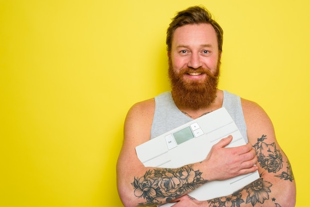 Happy man with beard and tattoos holds an electronic balance