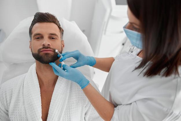수염을 기른 행복한 남자는 미용 클리닉에서 팔자주름 필러 시술을 받는다
