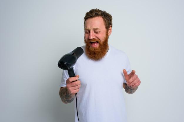 Счастливый человек с бородой использует фен как микрофон и танцует