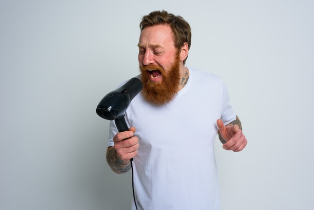 Happy man with beard use hair dryer as microphone and dances