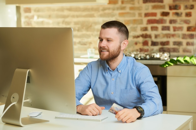 A happy man with a beard waits for an auction in front of the computer and holds a credit card at home