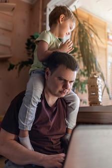 Счастливый человек с детьми, используя ноутбук и наушники во время домашней работы, жизни в карантине