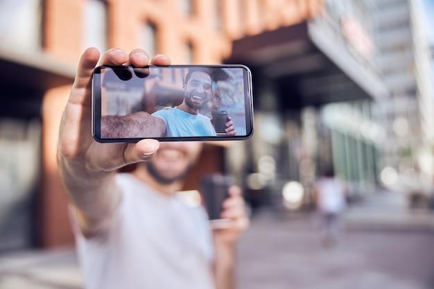 거리에서 selfie를 복용하는 커피와 함께 행복 한 사람