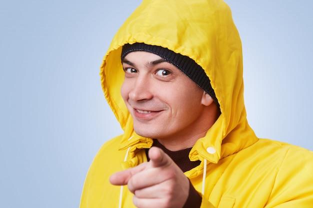Счастливый человек с темными привлекательными глазами носит желтое пальто с анораком, указывает указательным пальцем прямо, выбирает кого-то, изолированного над синей стеной. выборочный фокус. мужчина показывает на тебя