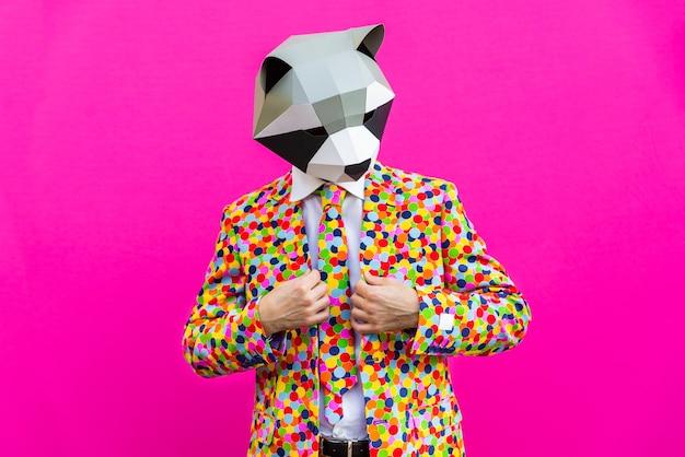 Счастливый человек с забавной низкой поли маской на цветном фоне
