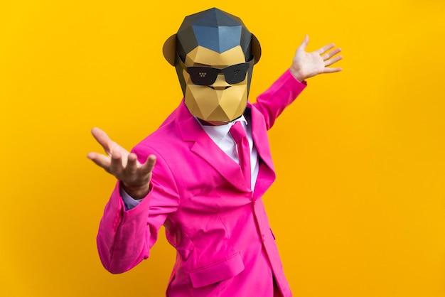 色付きの壁に面白い低ポリマスクを持つ幸せな男