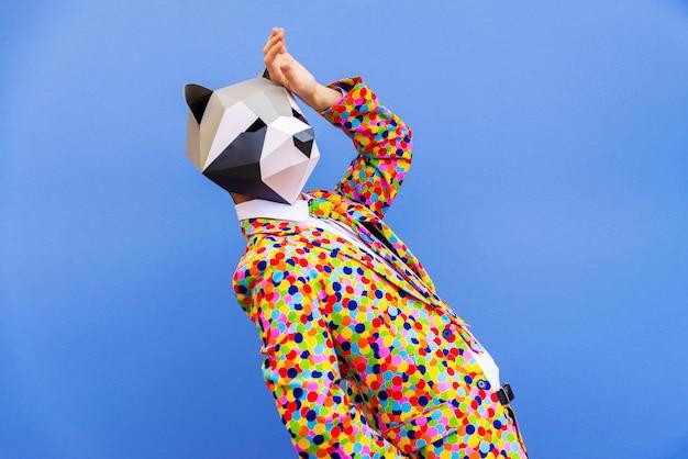 색된 벽에 재미있는 낮은 폴리 마스크와 함께 행복 한 사람