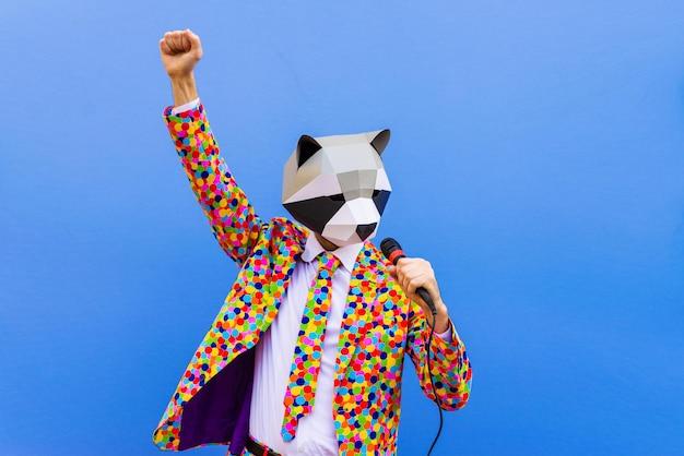 Счастливый человек с забавной низкой поли маской на цветной стене