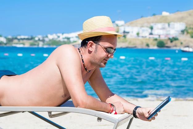 Felice l'uomo con il cappello con il suo smartphone