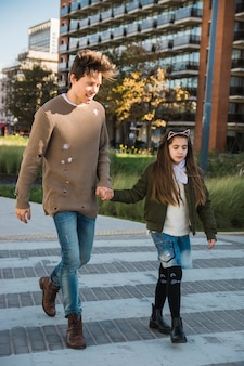 Happy man with his daughter walking together on pavement
